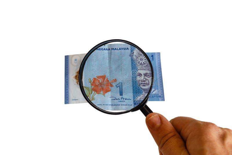 Una fattura e lente d'ingrandimento di ringgit della Malesia a disposizione immagine stock