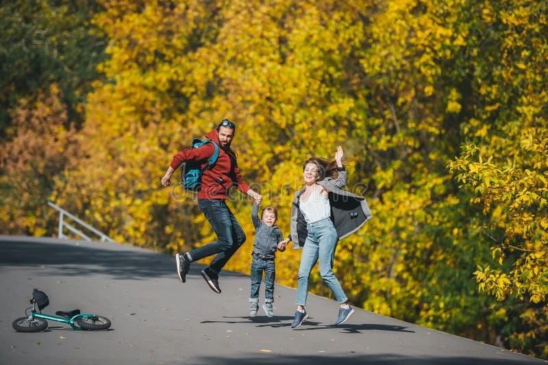 Una felice famiglia di tre persone che saltano su una strada rurale per il sole autunnale fotografia stock