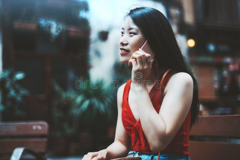 Una femmina asiatica sta telefonando all'aperto fotografia stock libera da diritti