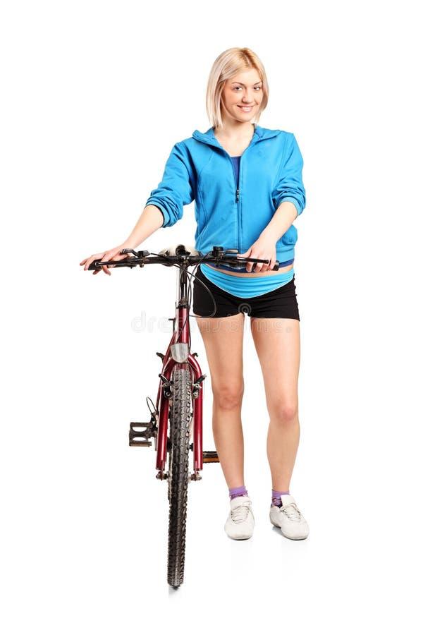 Una femmina bionda che propone vicino ad una bicicletta fotografia stock