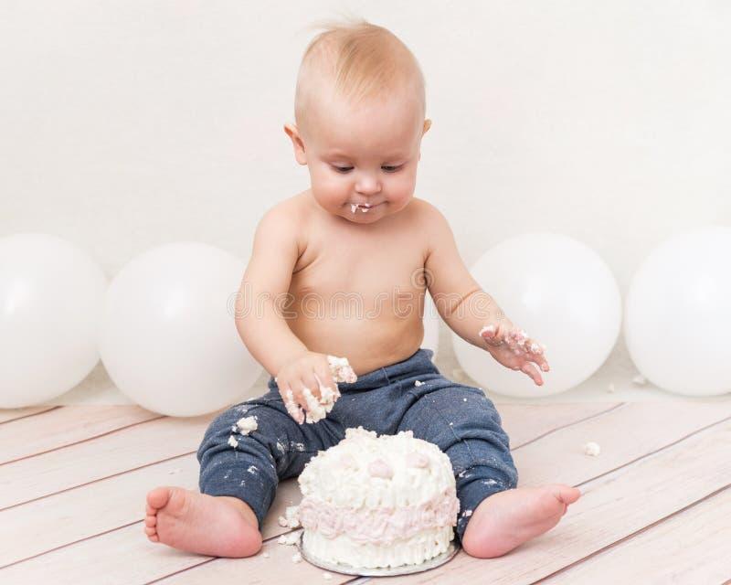 Una festa di compleanno del bambino di anno Bambino che mangia torta di compleanno Il ragazzo su un fondo leggero con gli impulsi fotografia stock libera da diritti