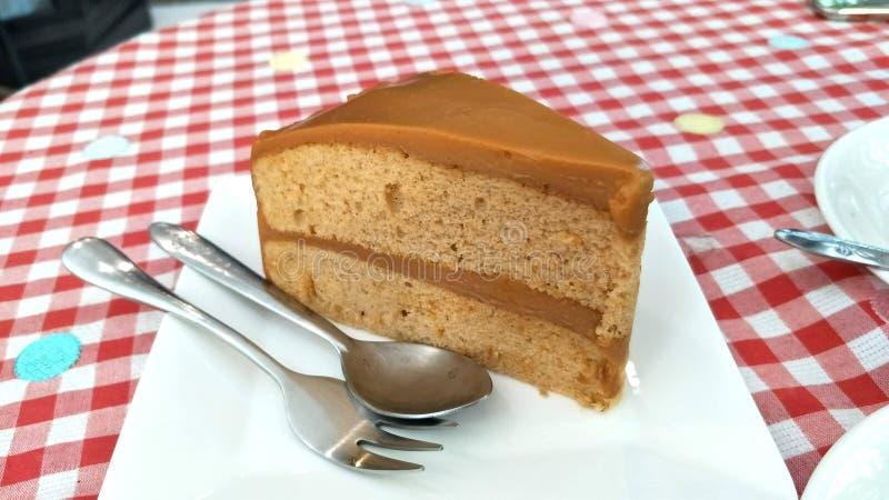 Una fetta di dolce di cioccolato casalingo sulla Tabella bianca del panno del plaid del percalle immagine stock libera da diritti