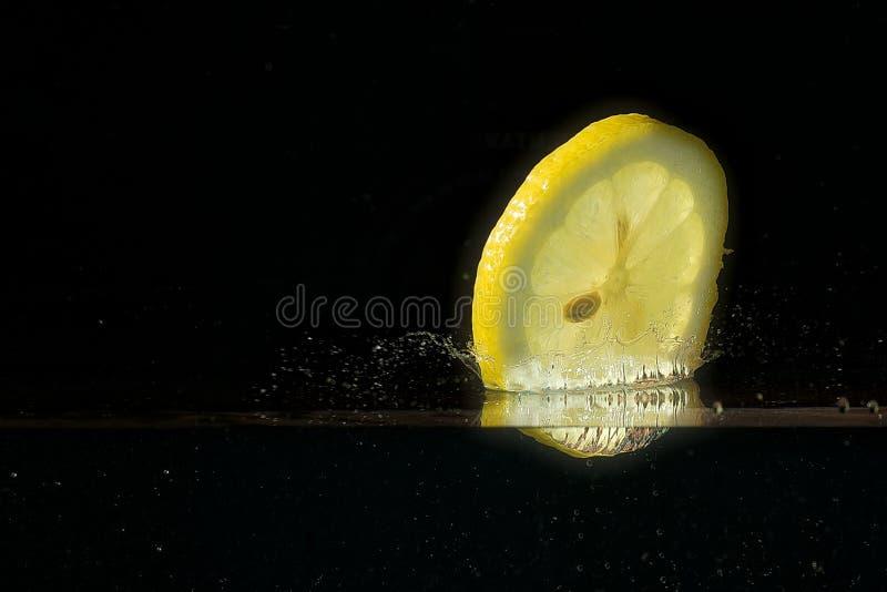 Una fetta di limone che immerge in acqua fotografia stock libera da diritti