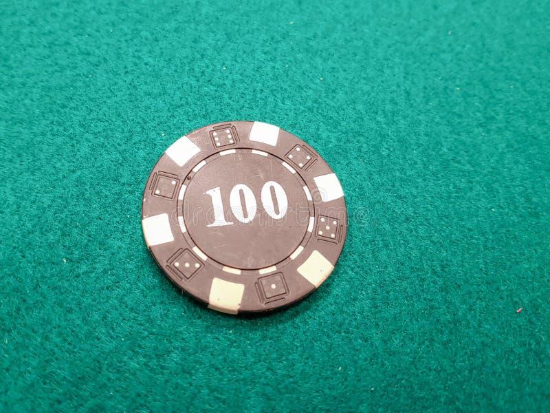 una ficha de póker negra de 100 en una estera verde del juego foto de archivo libre de regalías