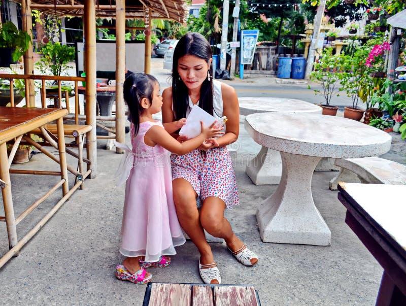 Una figlia amorosa presenta sua madre con un biglietto di auguri per il compleanno ad un ristorante all'aperto in Tailandia fotografia stock