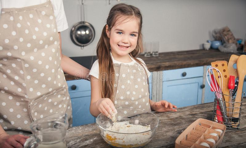 Una figlia dolce mescola le uova e la farina in una ciotola La ragazza sta andando fare il mafina con sua madre immagini stock