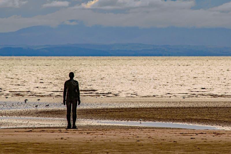 Una figura de la silueta que hace frente al horizonte en la playa de Crosby, Inglaterra fotos de archivo libres de regalías