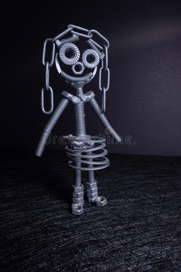 Una figura de un peque?o robot montado de varios pernos y nueces que se colocan en una posici?n vertical Simboliza tecnolog?a, foto de archivo