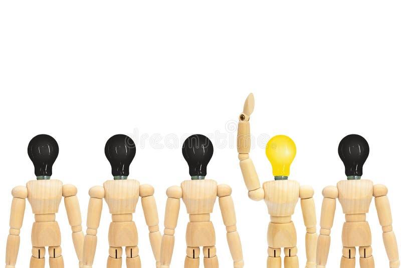 Una figura di legno manichino con la testa della lampadina della luce gialla che sta fuori fila di altre figure con la lampadina  immagini stock libere da diritti