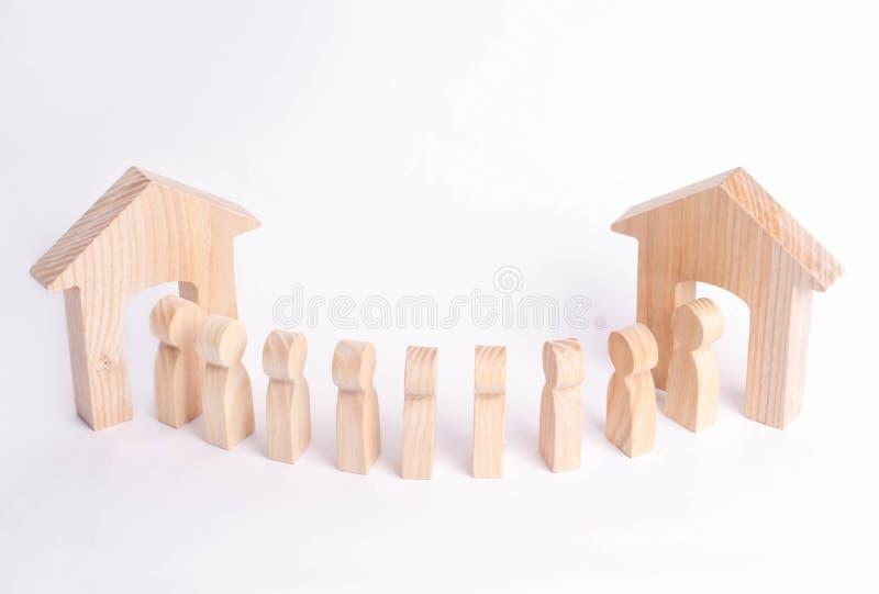 Una figura di legno di un uomo incontra un ospite su un fondo bianco Casa di legno Il concetto di un condominio, bene immobile ac immagini stock libere da diritti