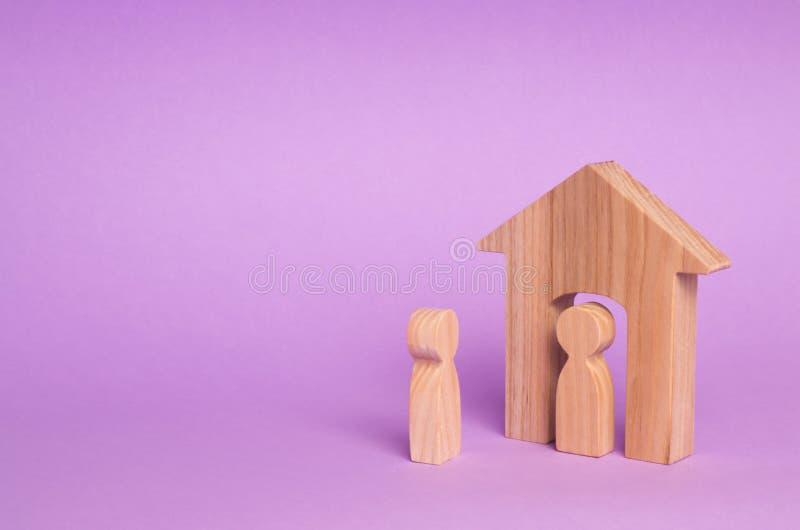 Una figura di legno di un uomo incontra un ospite su un fondo porpora Casa di legno Il concetto di un condominio, bene immobile fotografie stock