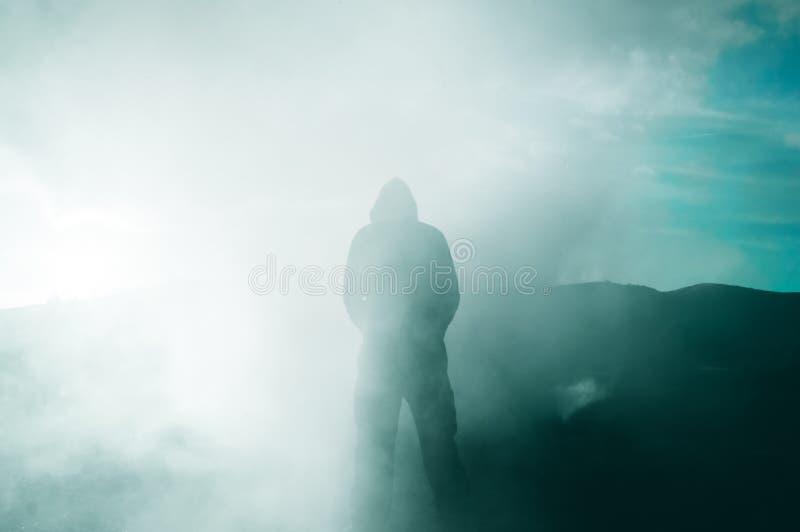 Una figura encapuchada silueteada por el sol como humo lo rodea fotografía de archivo