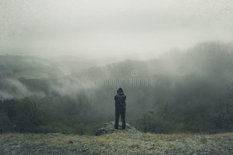 Una figura encapuchada solitaria encima de una colina, mirando hacia fuera a través del campo en un día de inviernos de niebla, l imágenes de archivo libres de regalías