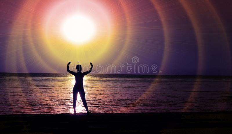 Una figura femenina teniendo en cuenta el resplandor cósmico de una estrella sobre la costa de la noche imagen de archivo