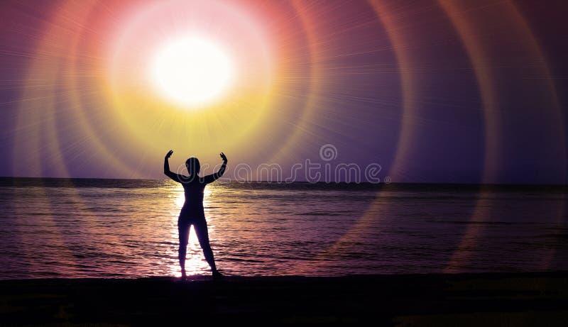 Una figura femminile alla luce dell'incandescenza cosmica di una stella sopra la costa di notte immagine stock