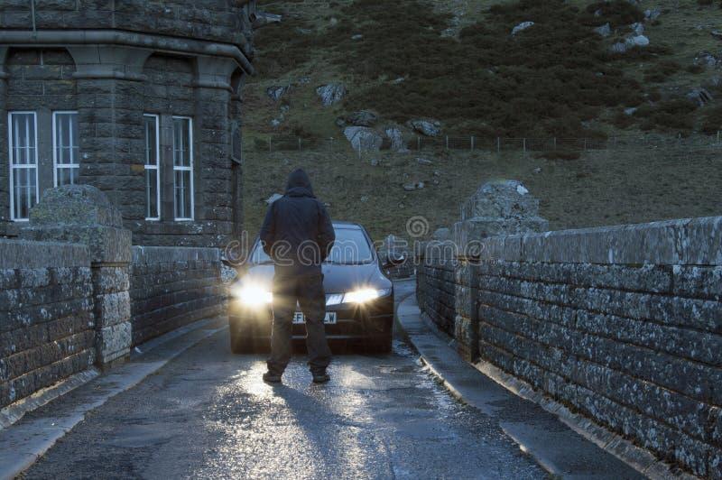 Una figura incappucciata sinistra in mezzo alla condizione della strada davanti ad un'automobile con i fari d'ardore immagine stock