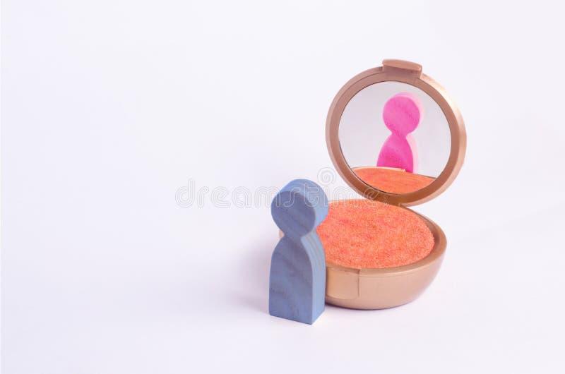 Una figura miniatura de un hombre mira en el espejo y considera el suyo que trama en otro género El concepto de identidad del gén foto de archivo