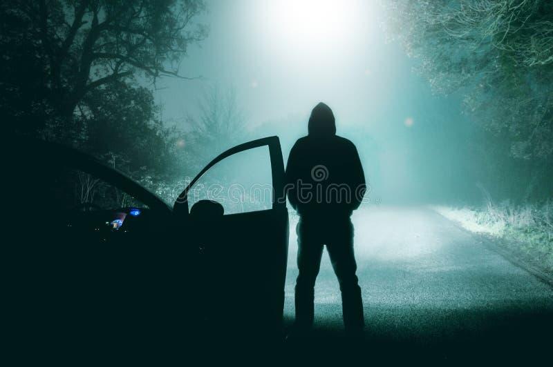 Una figura sola e incappucciata condizione accanto ad un'automobile che esamina una strada campestre nebbiosa vuota di inverno pr immagine stock libera da diritti
