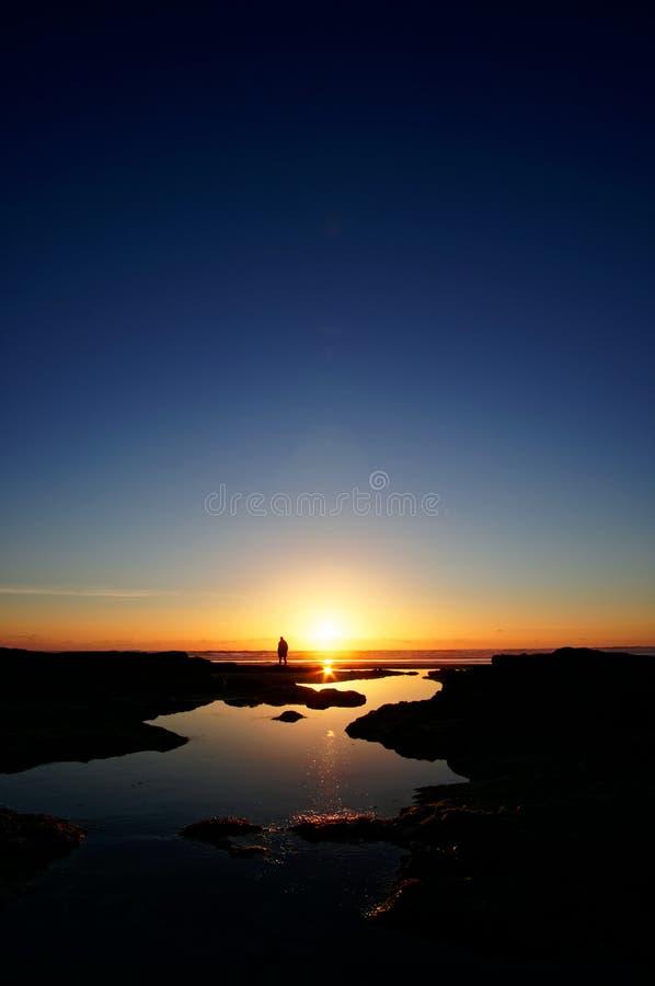 Una figura solitaria delante de una puesta del sol fotos de archivo