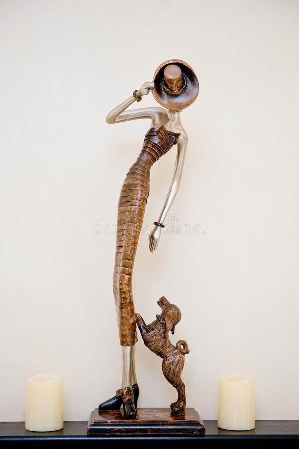 Una figurilla de una señora con un perro es alta y hermosa en una repisa con las velas foto de archivo