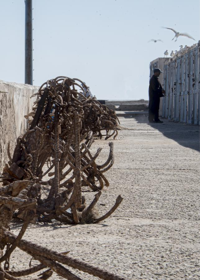 Una fila de anclas oxidadas, usada para cargar lobsterpots, se sienta al lado de los armarios para hombre del pescador fotos de archivo libres de regalías