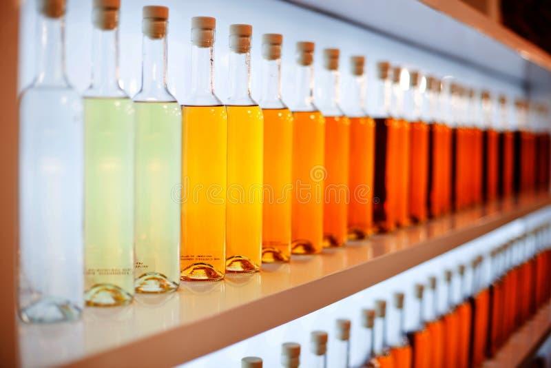 Una fila de botellas coloreadas con el coñac fotos de archivo