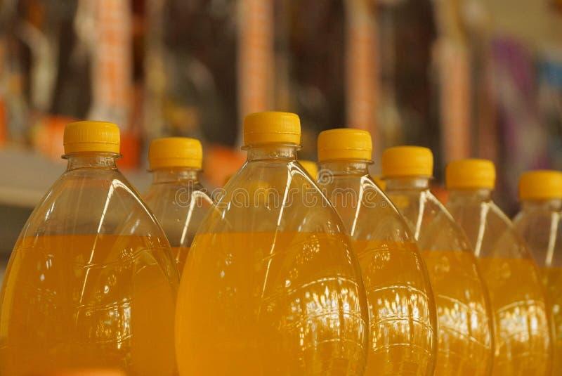 Una fila de botellas plásticas cerradas con la bebida amarilla fotografía de archivo
