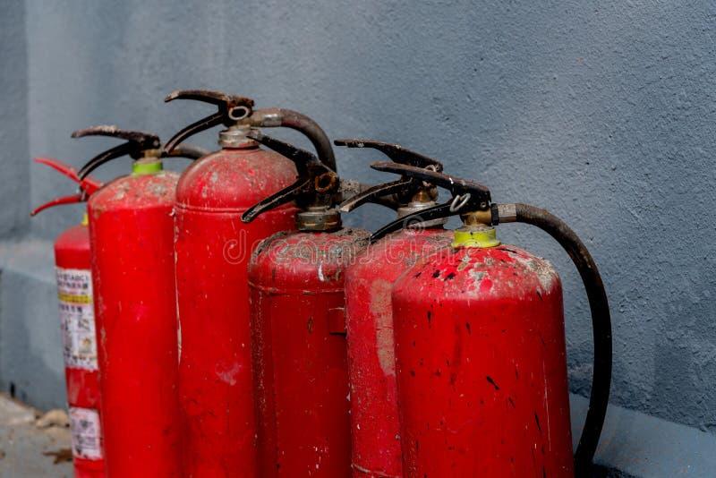 Una fila de extintores contra la pared foto de archivo