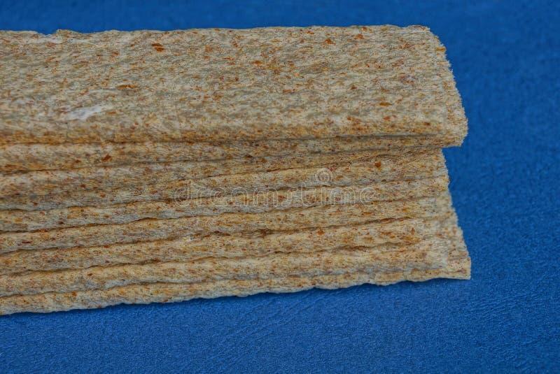 Una fila de galettes secos largos en una tabla azul imagen de archivo libre de regalías