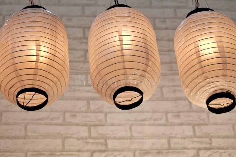 Una fila de lámparas de papel orientales con la luz caliente que cuelga del techo del sitio foto de archivo