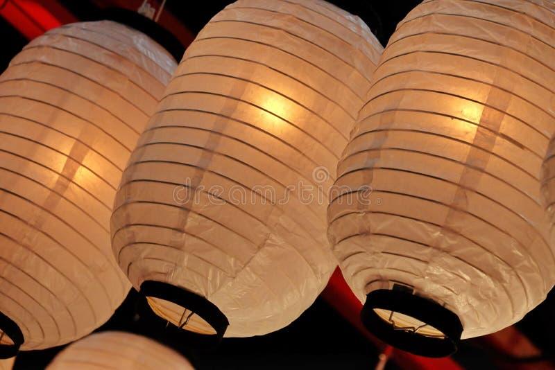 Una fila de l?mparas de papel orientales con la luz caliente que cuelga del techo del sitio fotos de archivo libres de regalías