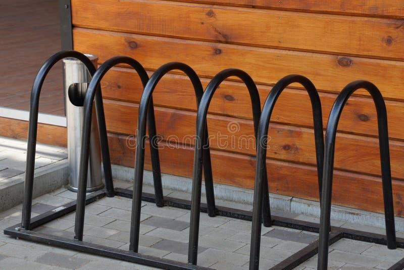Una fila de las barras de metal negras de un aparcamiento de la bicicleta en la acera foto de archivo libre de regalías