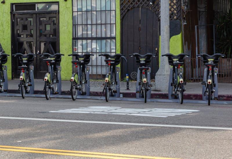 Una fila de las bicis del metro para el alquiler en una acera fotografía de archivo libre de regalías