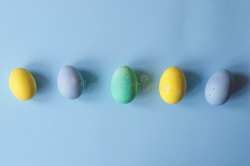 Una fila de los huevos de Pascua multicolores en un fondo azul fotografía de archivo libre de regalías