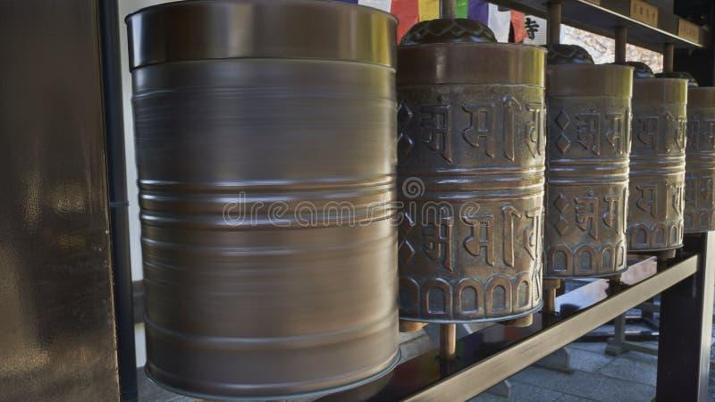 Una fila de ruedas de rogación budistas, una de ellas está haciendo girar imágenes de archivo libres de regalías