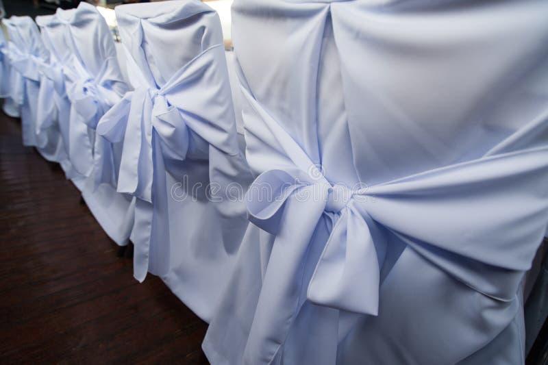 Una fila de sillas festivas en las cubiertas blancas imágenes de archivo libres de regalías