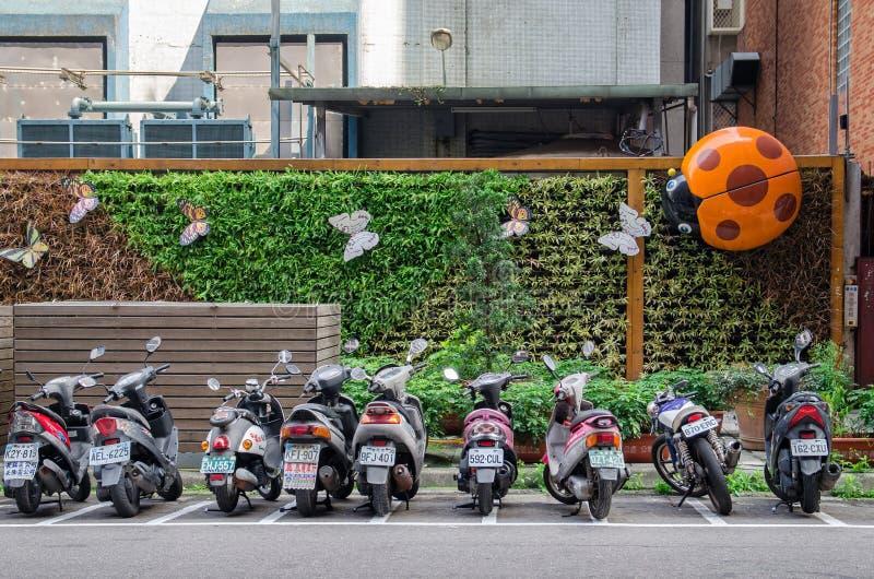 Una fila del estacionamiento de la motocicleta a lo largo del borde de la carretera en la calle de Taipei fotografía de archivo