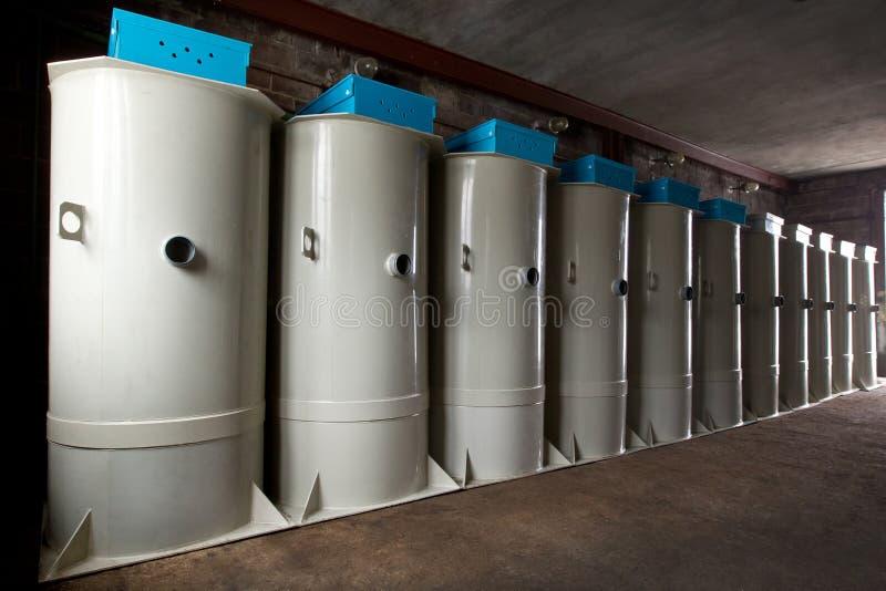 Una fila del sistema de aguas residuales autónomo europeo de las estaciones del tanque séptico en el almacén fotos de archivo libres de regalías