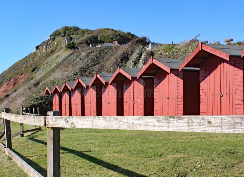 Una fila delle capanne della spiaggia sulla spiaggia dell'assicella a Branscome in Devon, Inghilterra fotografie stock