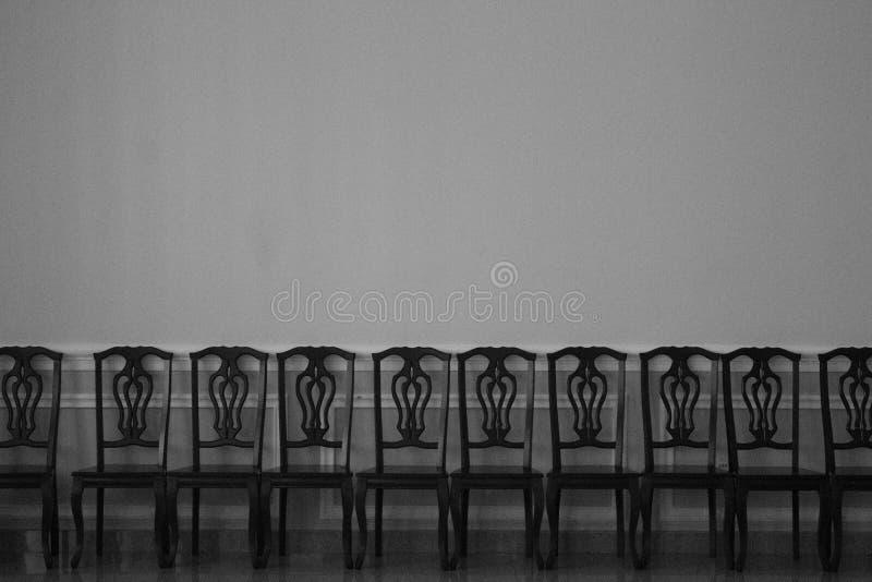 Una fila delle sedie nei precedenti della stanza illustrazione di stock
