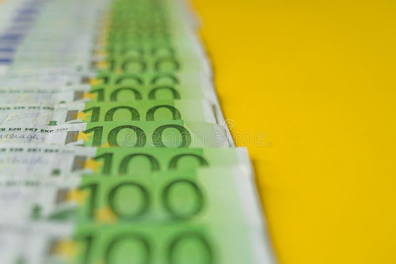 Una fila di cento banconote dell'euro, soldi di Unione Europea, su un fondo giallo immagine stock libera da diritti