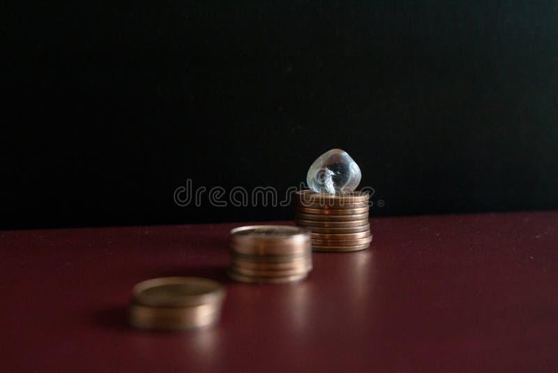 Una fila di 3 piccole pile di euro monete dei soldi e di pietra preziosa di cristallo immagini stock libere da diritti