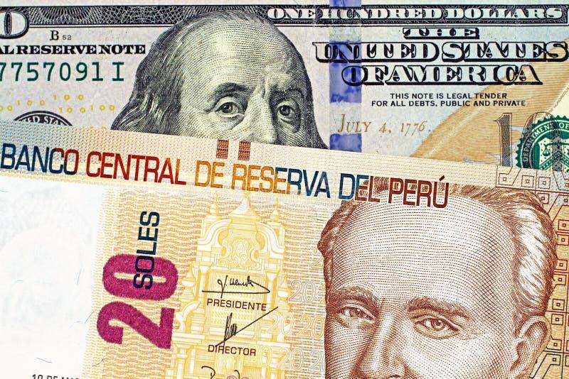Una fine su sull'immagine di una banconota peruviana con le cento banconote in dollari americana fotografia stock
