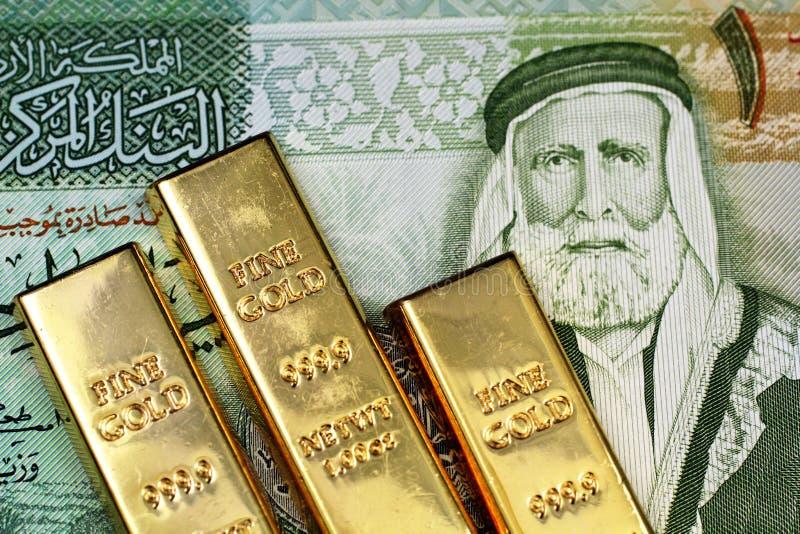 Una fine sull'immagine di un dinaro giordano con le piccole barre di oro fotografia stock