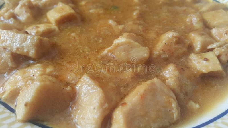 Una fine sulla vista dei cubi stufati della carne di pollo con le spezie su  fotografia stock