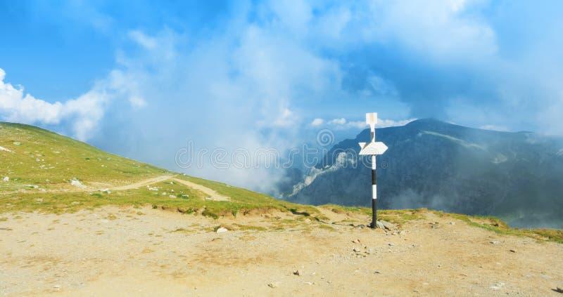 Una flecha blanca de la muestra de la dirección del poste indicador cerca de la trayectoria de seguimiento en fotos de archivo