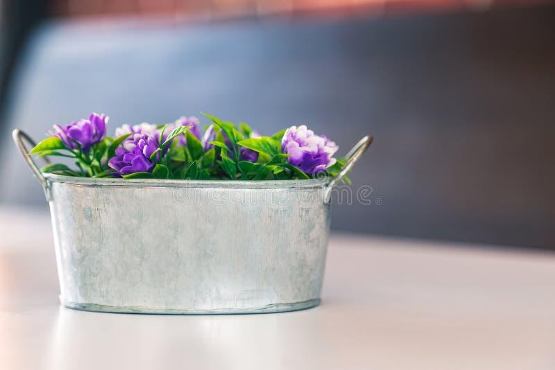 Una flor artificial en cubo del metal en la tabla blanca fotografía de archivo libre de regalías