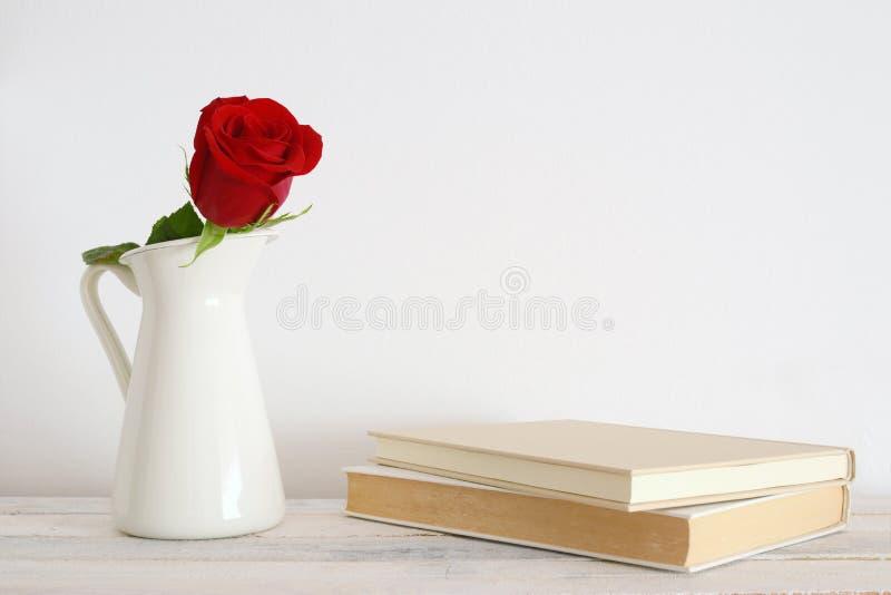 Una flor roja de la rosa en un florero blanco imagen de archivo