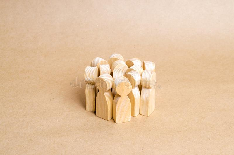 Una folla delle figure di legno della gente sta in un mucchio su un fondo di carta beige Il concetto di coesione e di cooperazion fotografia stock libera da diritti