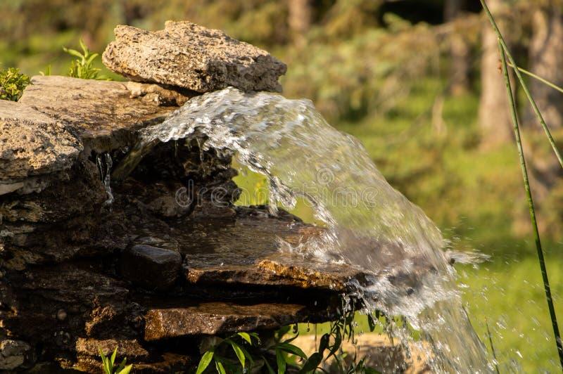 Una fontana nei bei scorrimenti dell'acqua del parco fotografia stock